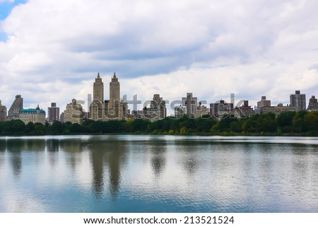 New York City Central Park's Onassis Reservoir and West Side midtown Manhattan skyline on a cloudy summer day. - stock photo