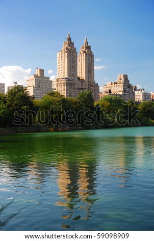 New York City Central Park urban Manhattan skyline with skyscrapers and trees lake reflection with blue sky and white cloud. - stock photo