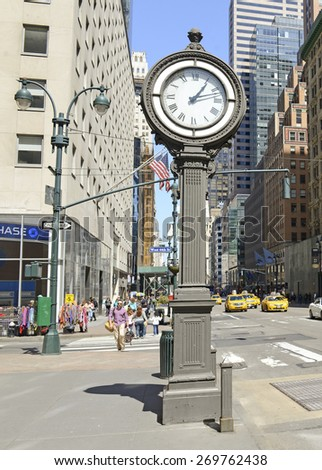 NEW YORK CITY - CIRCA APRIL 2015.  The cast iron Sidewalk Clock on 5th Avenue is a vintage part of the city, located amid the retail crowds and traffic along one of the busier streets of Manhattan. - stock photo