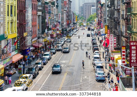 NEW YORK CITY - CIRCA JULY 2015: Tourists shop at businesses along a busy street in historic Chinatown during 4th of July festivities in Manhattan, New York City. - stock photo