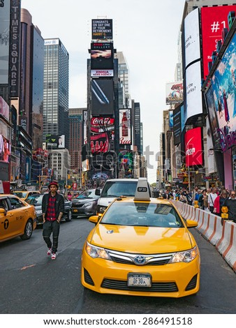 NEW YORK CITY - CIRCA MAY 2015: Yellow cab in Times Square, a busy tourist intersection of commerce Advertisements and a famous street of New York City and US