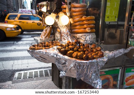 NEW YORK CITY - DEC 13:  Chestnuts roasting on street vendor food cart in Manhattan on Dec 13, 2013.  Roasted chestnuts are a seasonal treat sold during the holiday season in New York City. - stock photo