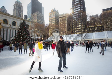 NEW YORK CITY - DEC 13: Ice skaters on Citi Pond in midtown Manhattan on Dec 13, 2013. This popular park is located behind NY Public Library features ice skating and holiday boutiques at Christmastime - stock photo
