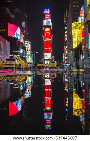 NEW YORK CITY - DECEMBER 19, 2016: Bright advertising signs and yellow taxis dominate a view of Times Square reflecting in a winter puddle.