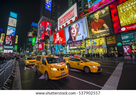 NEW YORK CITY - DECEMBER 22, 2015: Bright signage flashes over holiday crowds and traffic as Times Square gets prepared for New Year's Eve celebrations.