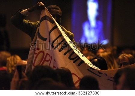 NEW YORK CITY - DECEMBER 13 2015: Former Secretary of State Hillary Rodham Clinton spoke at the National Immigration Integration conference. Activists with banner to protest during Mrs. Clinton's talk