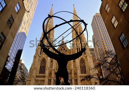 New York City - December 26, 2014:  Saint Patrick's Cathedral seen through the famed statue of Atlas Holding the World at Rockefeller Center on Fifth Avenue - stock photo