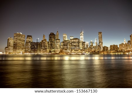New York City. Delightful Manhattan downtown skyline at dusk with skyscrapers illuminated over East River panorama. - stock photo