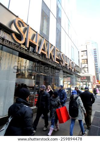 NEW YORK CITY - FEB. 25, 2015:  Pedestrians walk past a Shake Shack restaurant. Shake Shack is a fast casual restaurant chain based in New York City   - stock photo