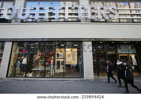 NEW YORK CITY - FEB. 25, 2015:  Pedestrians walk past an Urban Outfitters store. Urban Outfitters, Inc. is an American clothing corporation headquartered in Philadelphia, Pennsylvania.   - stock photo