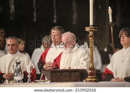 "NEW YORK CITY - FEBRUARY 18 2015: Ash Wednesday was celebrated at Trinity Church with a mass conducted by Bishop Andrew Dietsche followed by ""Ashes to Go"" on Broadway & Wall Bishop Dietsche at alter - stock photo"
