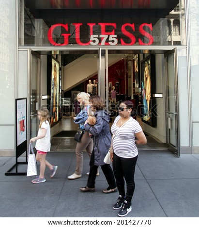 NEW YORK CITY - FRIDAY, MAY 8, 2015:  Pedestrians walk past a Guess Clothing retail store in Manhattan. Guess is an American upscale clothing brand and retailer.    - stock photo