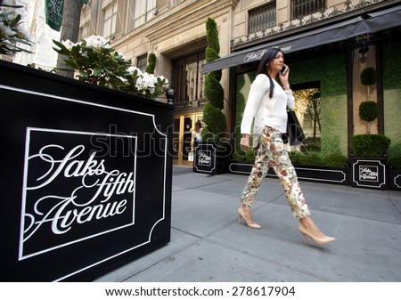 NEW YORK CITY - FRIDAY, MAY 8, 2015: Pedestrians walk past Saks Fifth Avenue in Manhattan. Saks Fifth Avenue is an American department store chain owned by the Hudson's Bay Company.