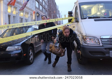 NEW YORK CITY - JANUARY 25 2015: a shooting at the Home Depot store in Chelsea left two employees dead in what is being called a murder-suicide. Employees duck under crime scene tape leaving scene - stock photo