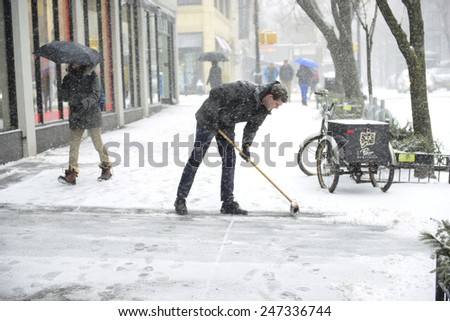 NEW YORK CITY - JANUARY 26 2015: Brooklyn Heights residents gird themselves in preparation for winter storm, Juno, the first major blizzard of 2015. Clearing sidewalks on Montague Street. - stock photo