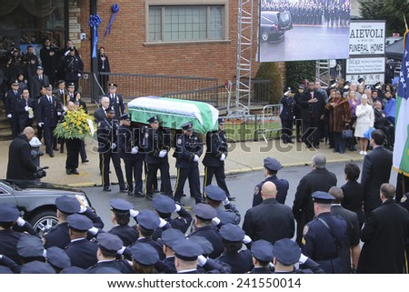 NEW YORK CITY - JANUARY 4 2015: several thousand police officers from all over North America attended funeral services for slain NYPD officer Wenjian Liu in Brooklyn. Family follows flag-draped coffin - stock photo