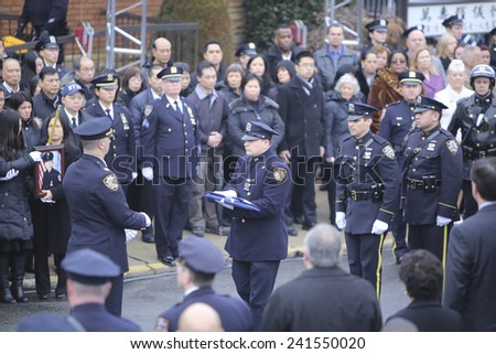 NEW YORK CITY - JANUARY 4 2015: several thousand police officers from all over North America attended funeral services for slain NYPD officer Wenjian Liu in Brooklyn. Presenting folded NYPD flag - stock photo