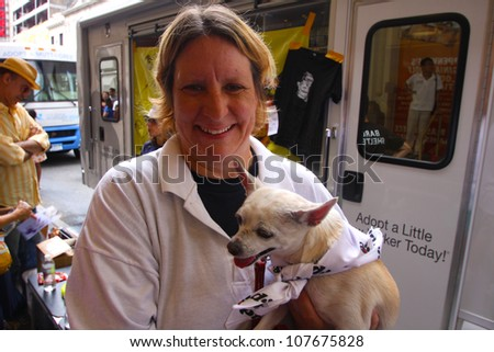 NEW YORK CITY - 14 JULY 2012: Broadway Barks marks its 14th year with a celebrity-studded adoption fair in Shubert Alley. BARC volunteer with friend on 14 July 2012 in New York City. - stock photo