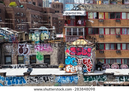 NEW YORK CITY - JULY 26, 2013:  Cityscape of lower Manhattan across graffiti covered buildings.  - stock photo