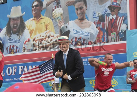 NEW YORK CITY - JULY 4 2014: Nathan's Famous held its annual Fourth of July Hotdog Eating Contest in Coney Island, Brooklyn despite moderate rain from Hurricane Arthur. MC George Shea on stage - stock photo