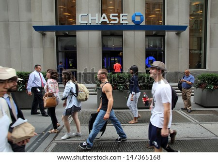 NEW YORK CITY - JULY 11: Pedestrians walk past a branch office of  Chase Bank in lower Manhattan on Thursday, July 11, 2013.  JPMorgan Chase & Co. is an American multinational bank. - stock photo
