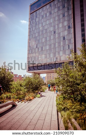 NEW YORK CITY - JULY 22: People walk along the High Line Park on July 22, 2014. The High Line is a popular linear park built on the elevated former New York Central Railroad spur in Manhattan. - stock photo