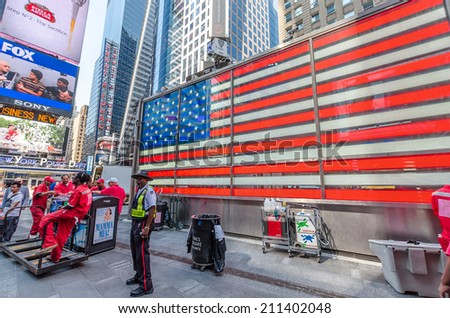 NEW YORK CITY - JULY 22: Police officer stands on Times Square on July 22, 2014 in New York. Times Square is a major commercial intersection in Manhattan, at the junction of Broadway and 7th Ave. - stock photo