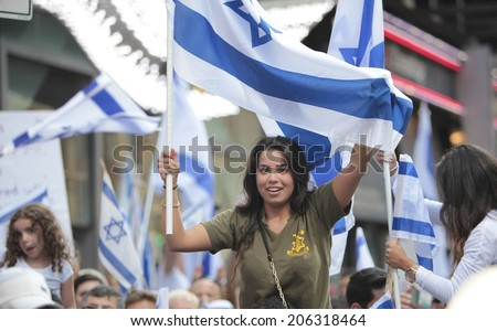 NEW YORK CITY - JULY 20 2014: Several thousand attended a rally in Times Square to support Israel's recent actions in Gaza. Female Israel supporter with Israeli flags - stock photo