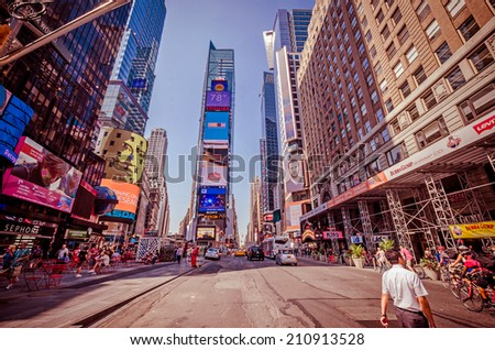 NEW YORK CITY - JULY 22: Undefined people pass through Times Square on July 22, 2014 in New York. Times Square is a major commercial intersection in Manhattan, at the junction of Broadway and 7th Ave. - stock photo