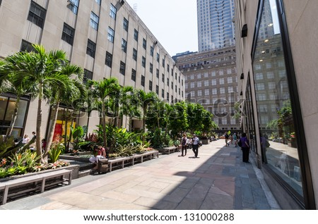 NEW YORK CITY - JULY 12: Walkway with palm trees near Rockefeller Center on July 12, 2012 in New York. Rockefeller Center is a complex of 19 commercial buildings covering 22 acres. - stock photo