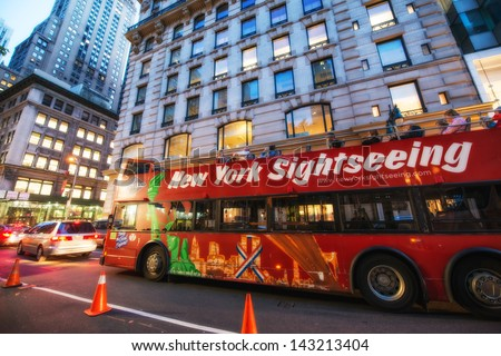 NEW YORK CITY - JUN 8; Famous Sightseeing red bus at sunset on city streets, June 8, 2013 in NYC. The red bus is the most appreciated by enthusiast tourists. - stock photo