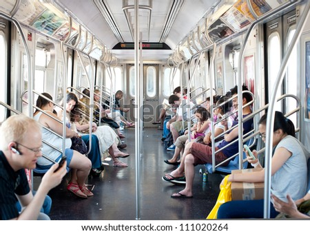 NEW YORK CITY - JUNE 29: Commuters in subway wagon on June 29, 2012 in NYC. The NYC Subway is one of the oldest and most extensive public transportation systems in the world, with 468 stations. - stock photo