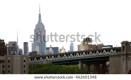 New York City - June 7 2016: Establishing shot of the Empire State Building standing tall over the Manhattan Bridge overpass as traffic travels into Brooklyn. Isolated against a bright white sky