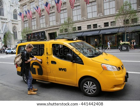 NEW YORK CITY - JUNE 16, 2016: Passenger hires New York City Taxi at the Fifth Avenue in Manhattan. New York has around 6,000 hybrid taxis the most in any city in North America - stock photo