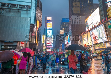 NEW YORK CITY - JUNE 13, 2013: Rainy night with tourists in Times Square. Times Square is a major commercial intersection and neighborhood in Midtown Manhattan.