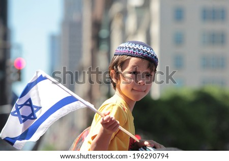 NEW YORK CITY - JUNE 1 2014: The 50th annual Israel Day Parade filled Fifth Avenue with politicians, revelers & a few protestors marking Israel's 66th anniversary. Little boy with cap & Israeli flag - stock photo