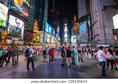NEW YORK CITY - JUNE 9: Times Square, is a busy tourist intersection of neon art and commerce and is an iconicplace of New York City and USA on June 9, 2014 in Manhattan, New York City. - stock photo