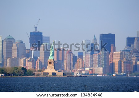 New York City lower Manhattan skyline with Statue of Liberty and urban city skyline over river panorama view. - stock photo