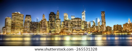 New York City. Magnificent Manhattan downtown skyline at dusk with skyscrapers illuminated over East River panorama. - stock photo