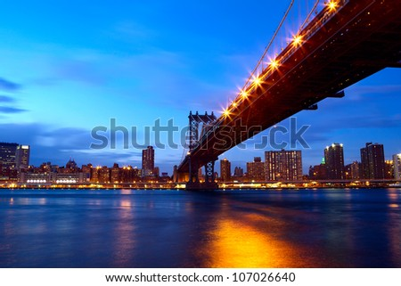 New York City Manhattan Bridge over East River with skyline after sunset