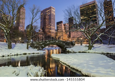 New York City Manhattan Central Park  in winter with snow, Gapstow bridge; freezing lake and skyscrapers at dusk.  - stock photo