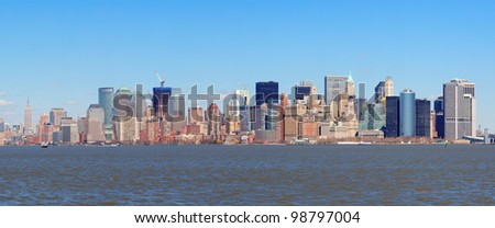New York City Manhattan downtown district skyline panorama with skyscrapers over river with blue clear sky. - stock photo
