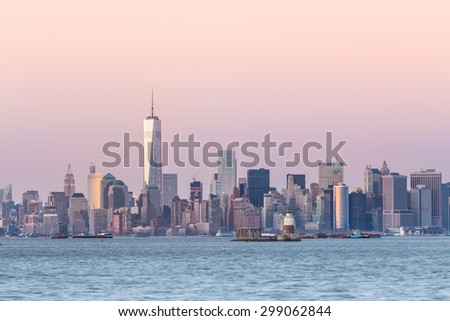 New York City Manhattan downtown skyline at dusk with skyscrapers illuminated over Hudson River panorama. Horizontal composition, copy space. - stock photo