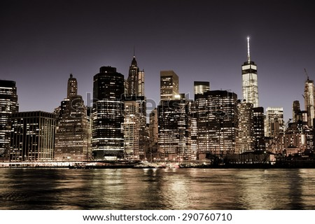 New York City Manhattan downtown skyline at night with illuminated skyscrapers, vintage filter - stock photo