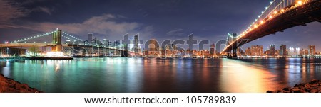 New York City Manhattan downtown skyline panorama with skyscraper and water reflection over East River at night