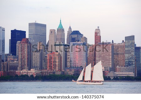 New York City Manhattan downtown skyline with boat at sunset over Hudson River panorama - stock photo