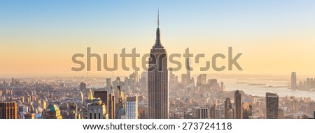 New York City. Manhattan downtown skyline with illuminated Empire State Building and skyscrapers at sunset. Panoramic composition. - stock photo