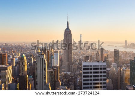 New York City. Manhattan downtown skyline with illuminated Empire State Building and skyscrapers at sunset. - stock photo