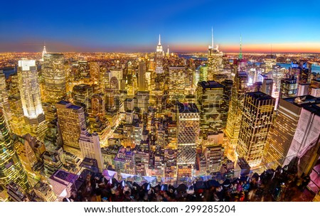 New York City. Manhattan downtown skyline with illuminated Empire State Building and skyscrapers at dusk seen from observation deck. Panoramic view. - stock photo