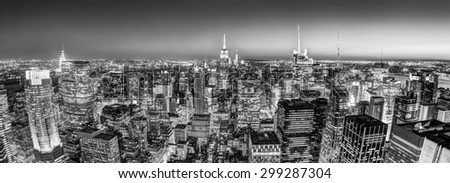 New York City. Manhattan downtown skyline with illuminated Empire State Building and skyscrapers at dusk seen from observation deck. Panoramic view. Black and white photo. - stock photo